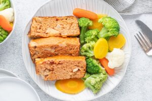 Sliced pieces of chicken meatloaf served on the plate with veggies