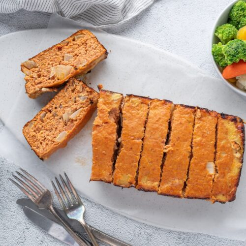 Sliced chicken meatloaf on the plate with forks and knifes beside the plate and on other site a bowl of veggies