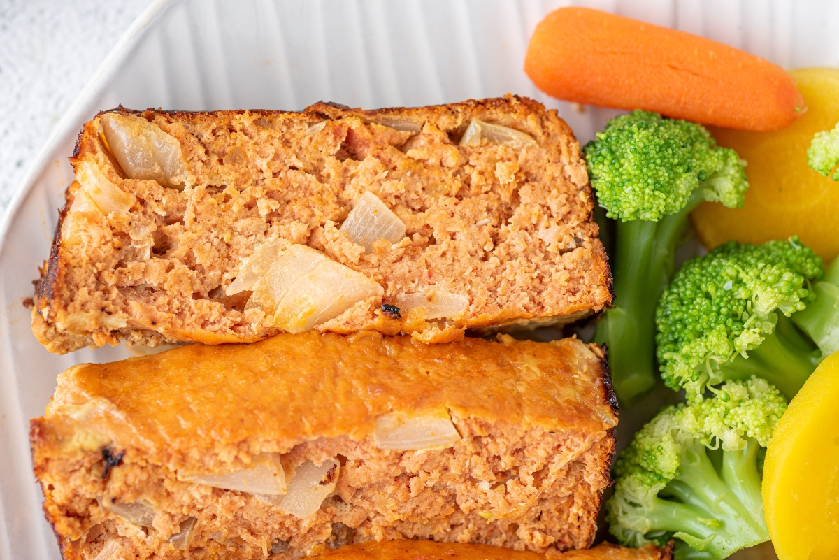 Two slices of chicken meatloaf served on the plate with veggies