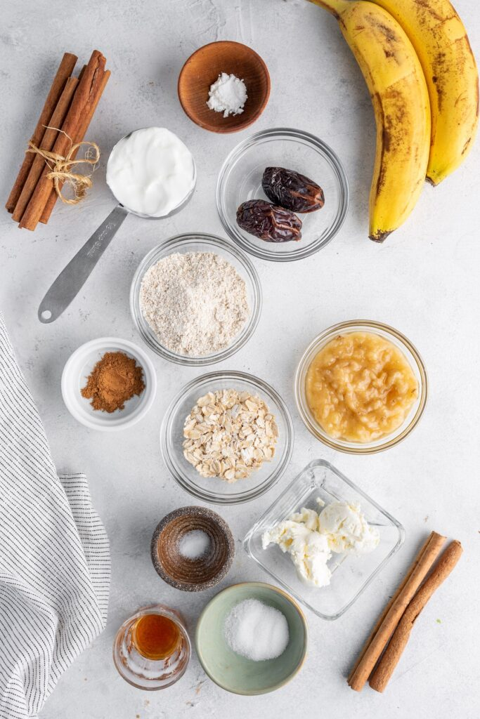 Food ingredients for cinnamon rolls - banana, flour, cinnamon sticks, oatmeal, cheese, dates in cups and bawls