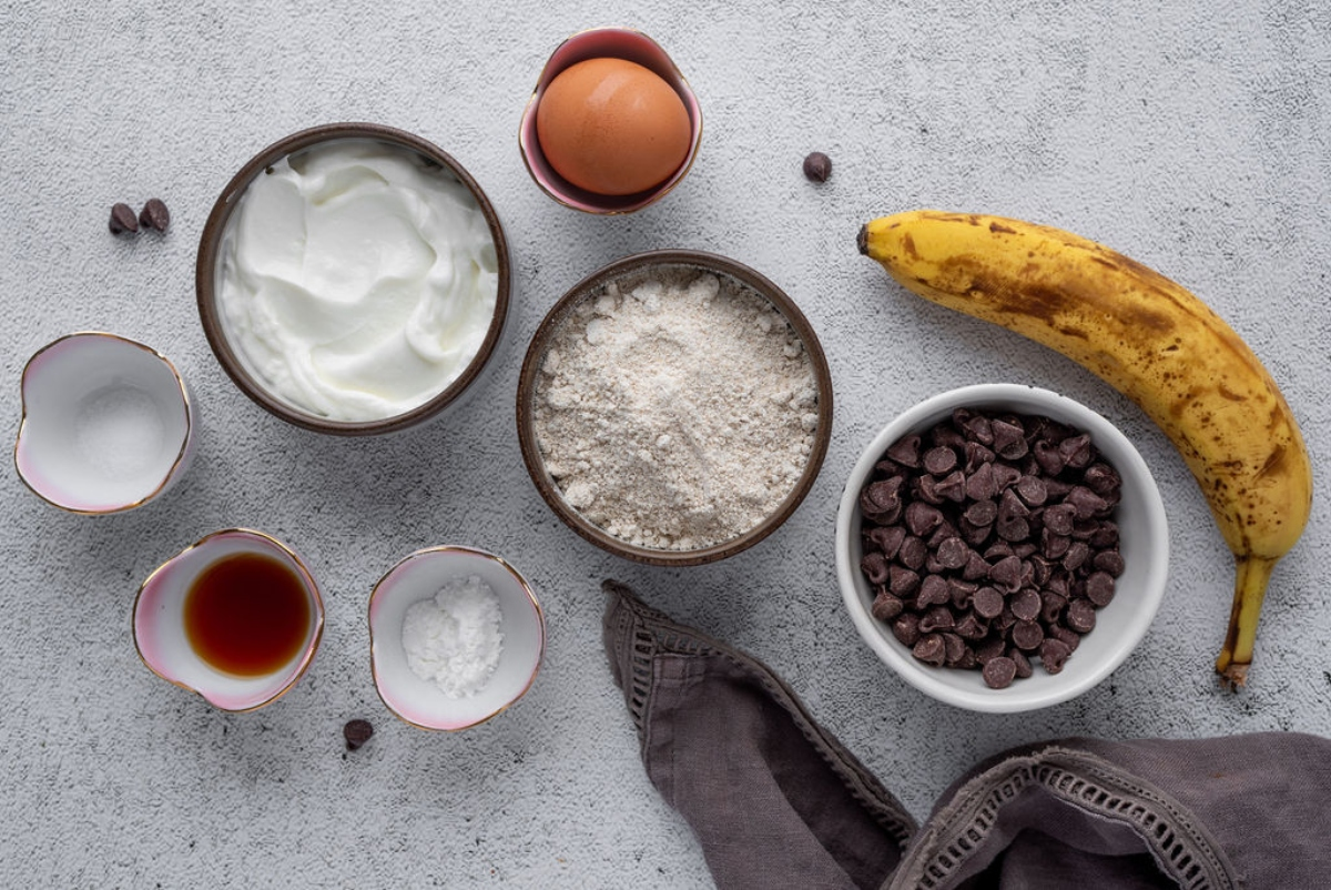 Food ingredients in bowls for banana cookies with chocolate chips, Greek yogurt, egg, banana, flour, chocolate chips, vanilla, baking powder, salt