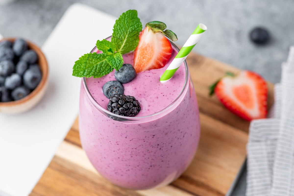 Berry smoothie that blasts belly fat in glass decorated with a straw, berries and mint