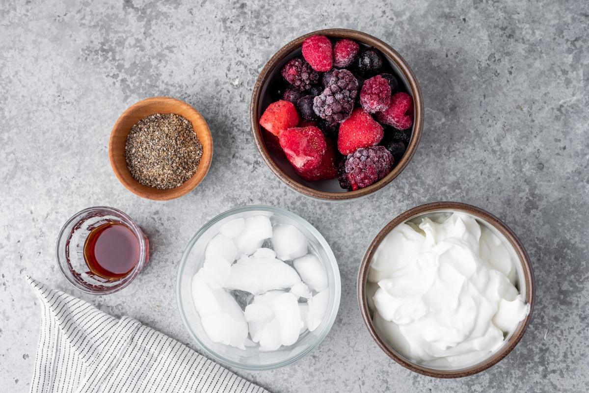 Bowl of ice, strawberries, chia seeds, Greek yogurt and shot of vanilla extract
