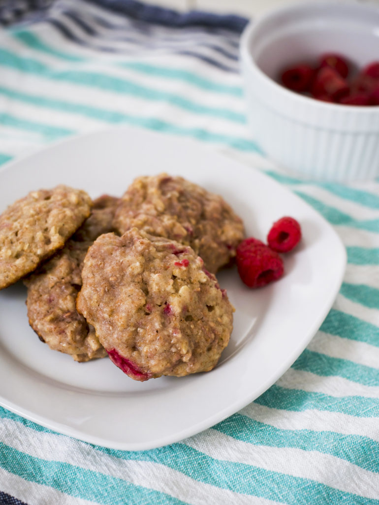 breakfast cookies on a white plate next to a bowl of raspberries