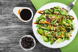 mixed lettuce, spinach, carrot, ham, cheese and prunes salad , top-view