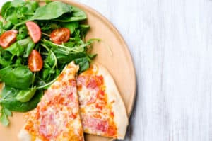 Pizza slices on plate with fresh side salad, overhead perspective with plenty of copy space on rustic white background