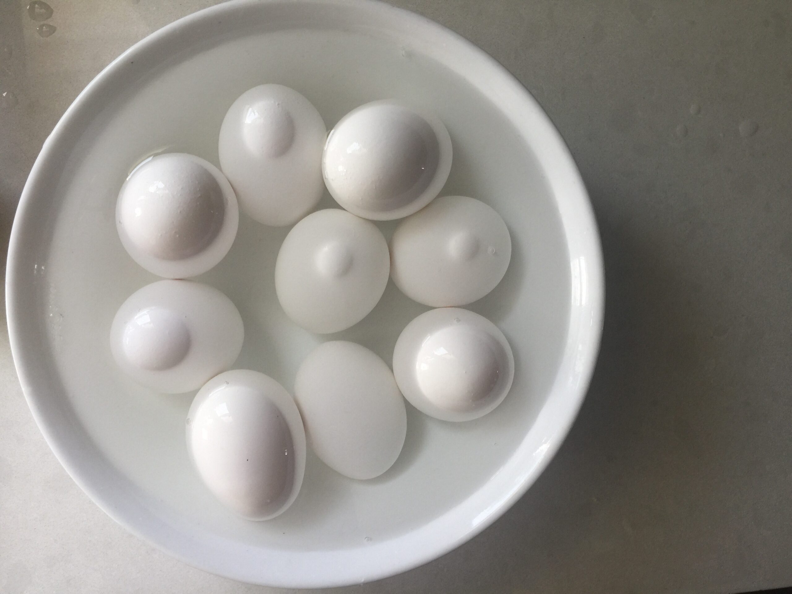Place baked eggs in an ice bath to cool to hard boil eggs in the oven