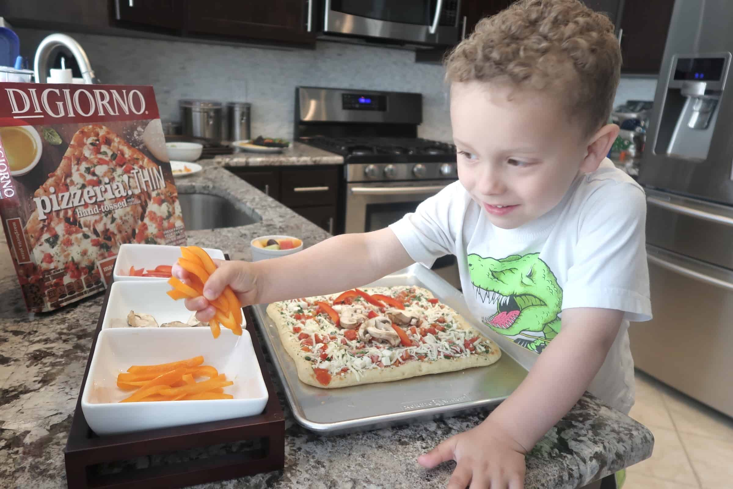 child adds vegetables to pizza