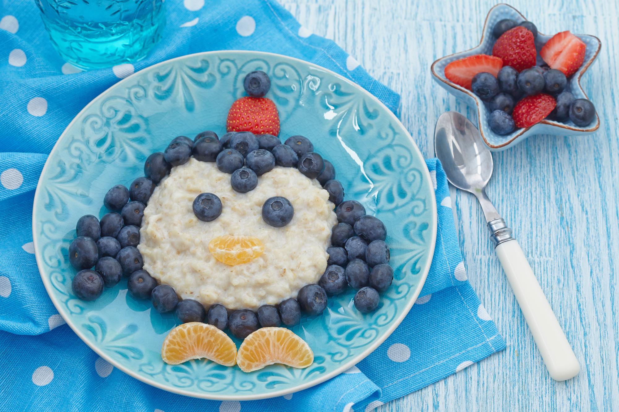 Funny kids breakfast porridge with fresh berries penguin food art penguin oatmeal breakfast