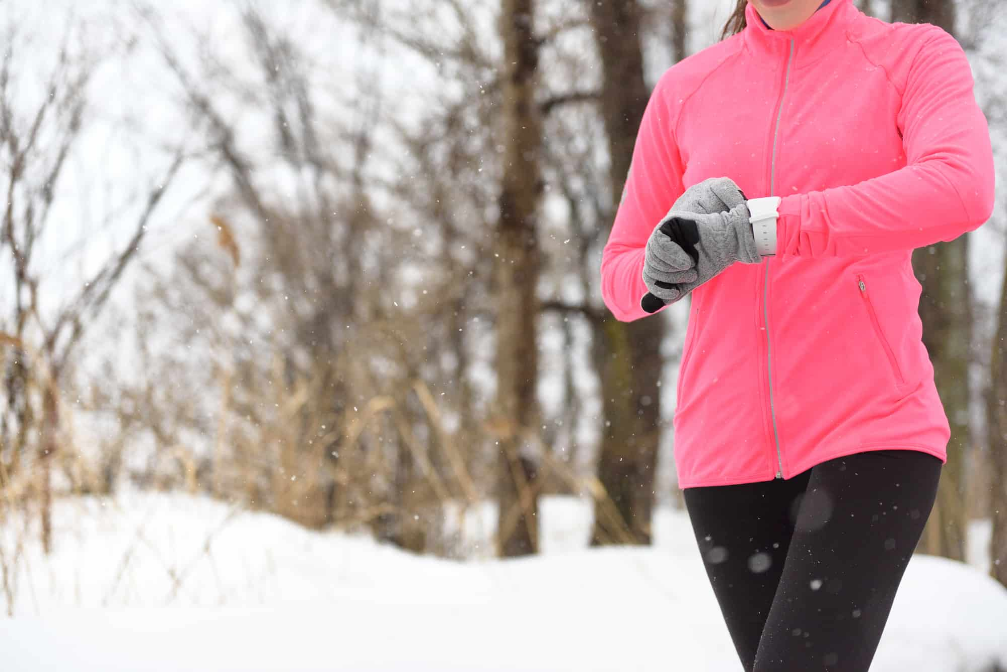 Runner using smartwatch jogging in snow trail in forest. winter weather closeup. Female athlete checking her cardio with a heart rate monitor during workout outside in running park.