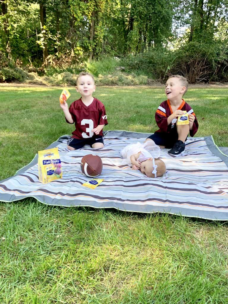 children eating a healthy afterschool snack on lawn playing football