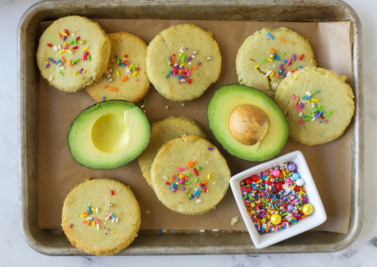 Keto sugar cookies with avocado cut in half and a cup of sprinkles on baking tray