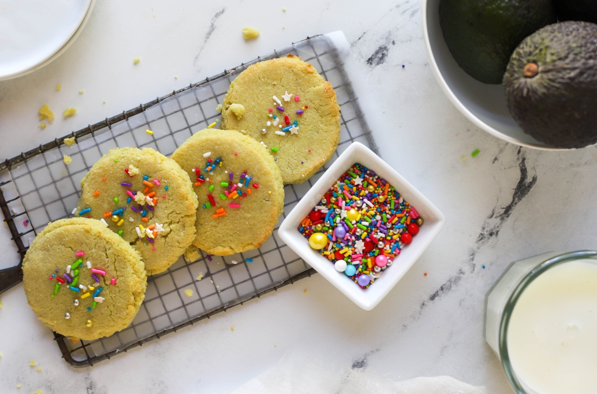 Keto sugar cookies with a cup of sprinkles, a bowl wit avocadoes and a bottle of milk beside