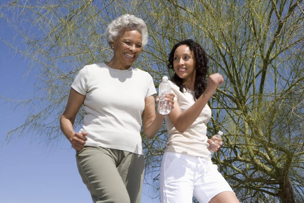 Happy African American mother and daughter jogging together against blue sky