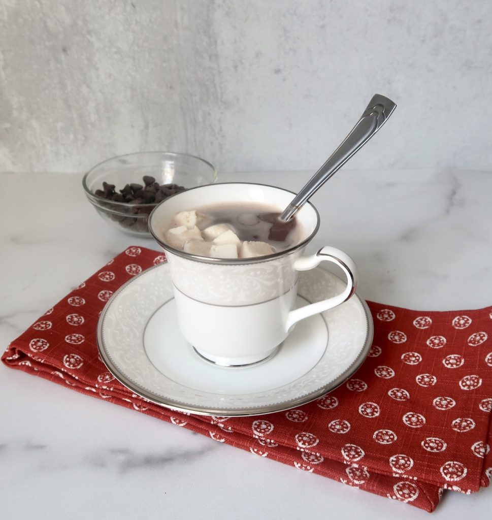 A glass of keto hot chocolate with low sugar marshmallows in in a white mug with a spoon placed on top of a red towel with chocolate chips in the background