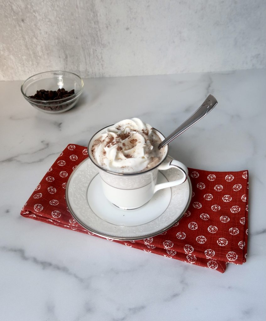 The DIY Keto Hot Cocoa has been prepared and placed in a white mug and topped with a whipped topping. A spoon in in the mug and the mug is placed on a red towel with chocolate chips in the background.