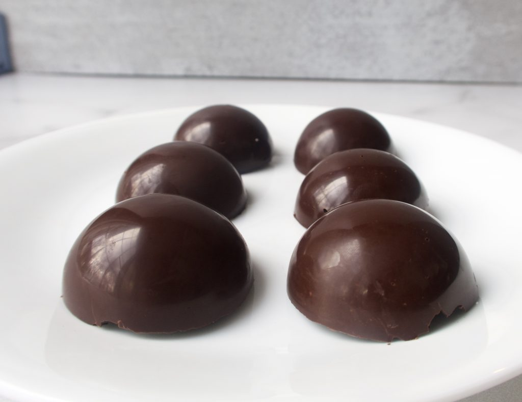 6 plain round chocolate shells on a white plate