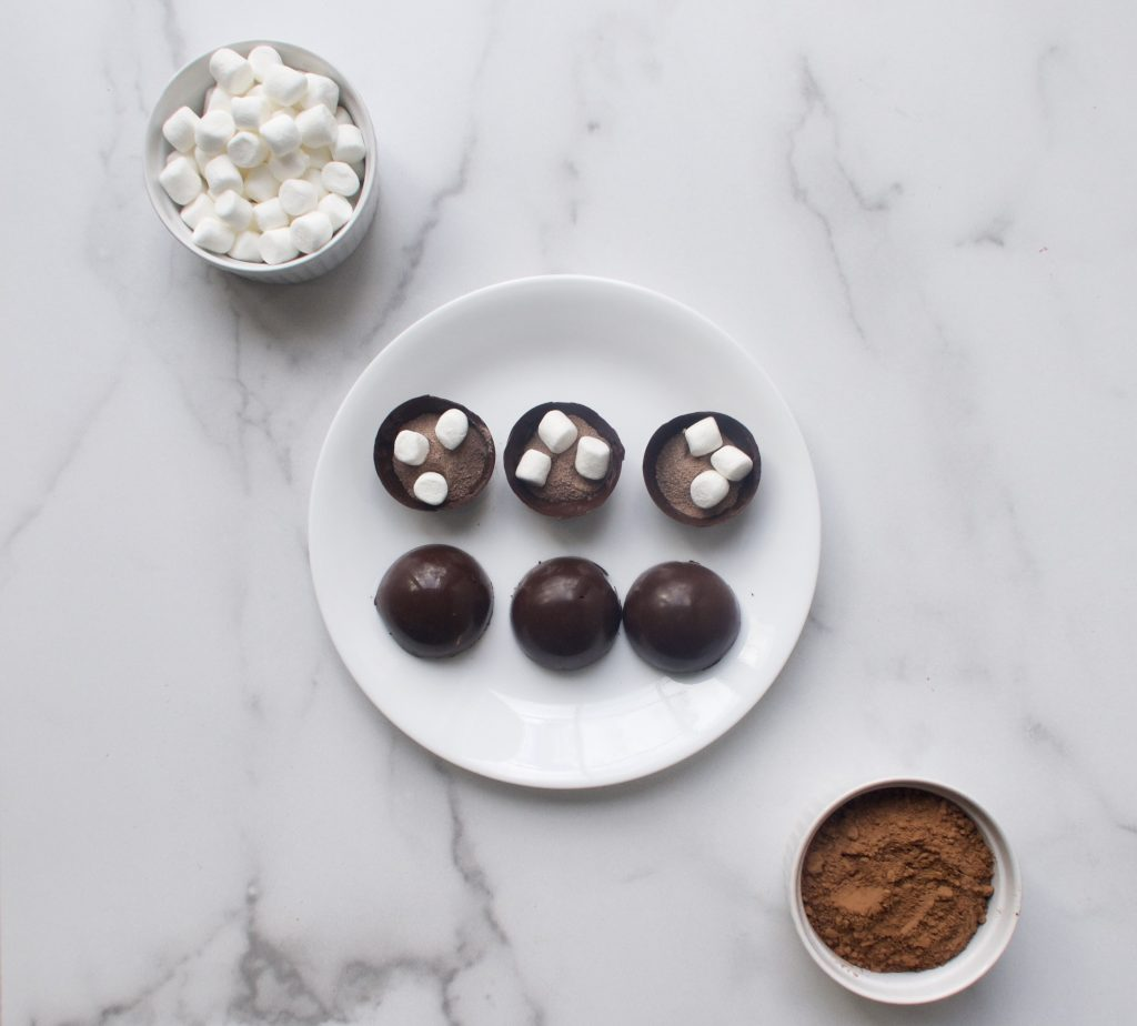 ingredients on a hot chocolate bomb on white plates and bowls on a marble surface
