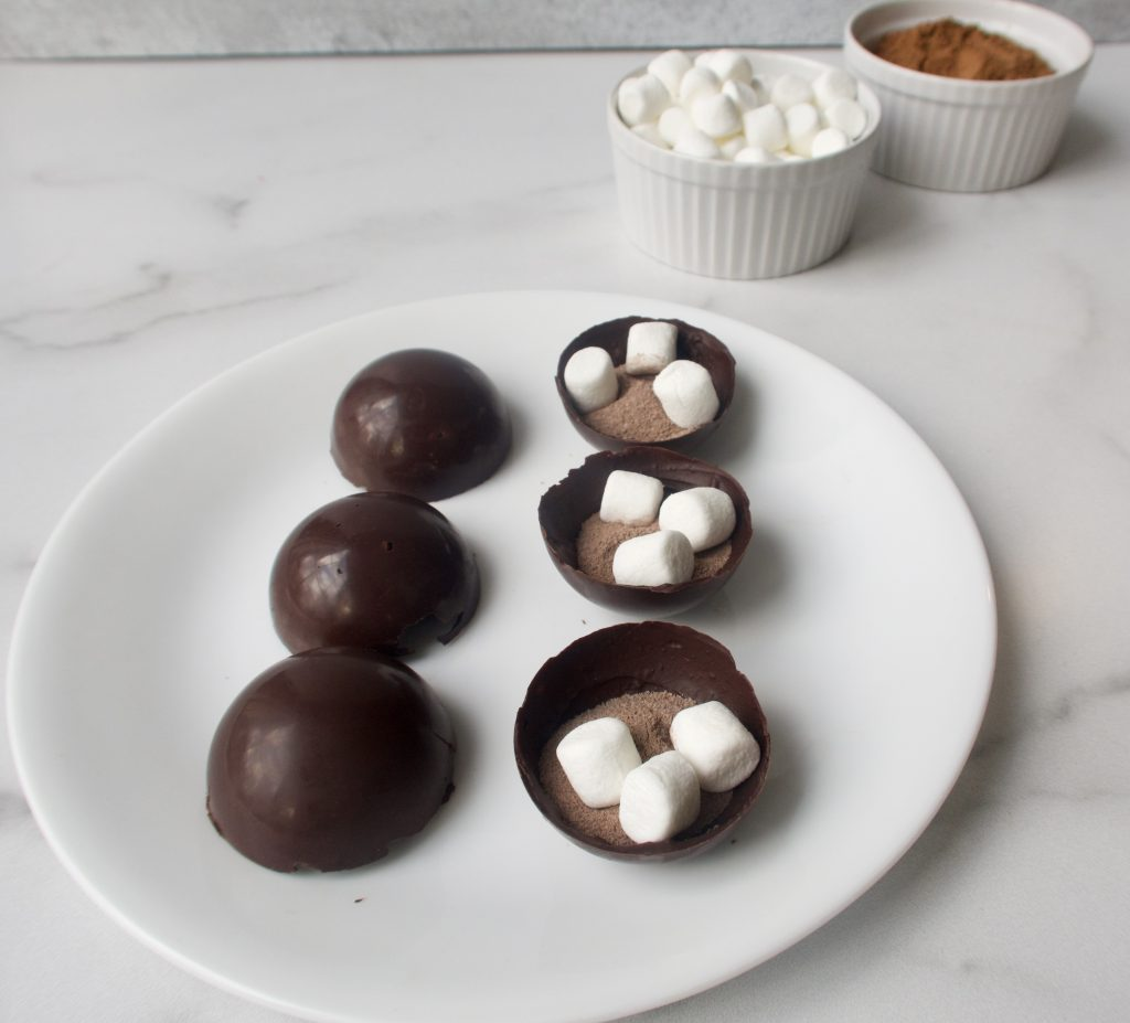 6 chocolate shells on a white plate with half of them filled with marshmallows and cocoa mix. two small bowls of ingredients in the background