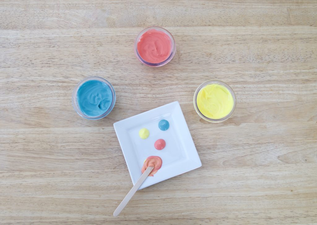 "blue, yellow, and red colored yogurt in 3 cups with white plate for ""painting"""