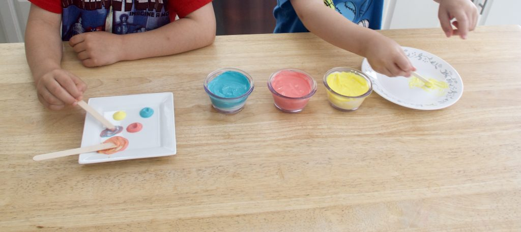 two kids painting with red, blue, and yellow colored yogurt