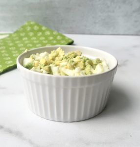 Avocado egg salad in white ramekin on marble counter with green towel in background