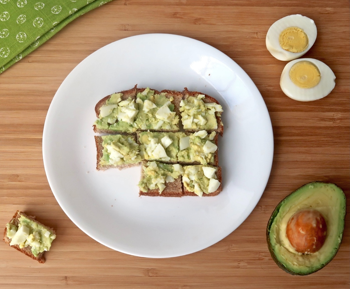 Avocado egg salad spread over toast that has been sliced into nine small squares with one square removed
