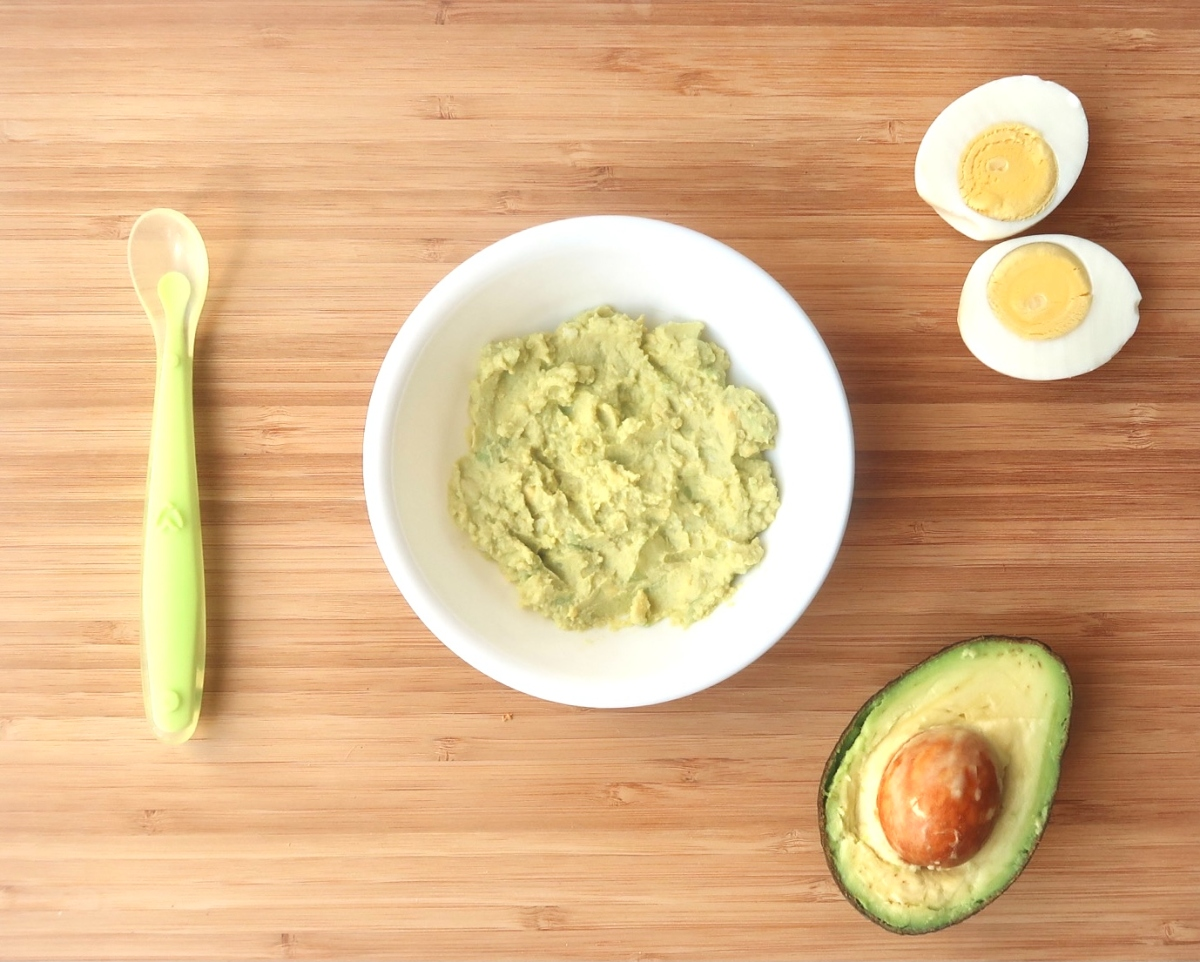 a white bowl of pureed egg salad sits next to a baby spoon with a sliced hard boiled egg and one half of an avocado on a wooden cutting board