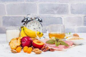Clock with glass of tea, glass of yogurt, bananas, plums, other fruits, nuts and bowl of seeds on table