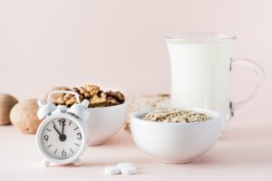 Clock with ball of oatmeal, ball of walnuts, pills and a jug of yogurt