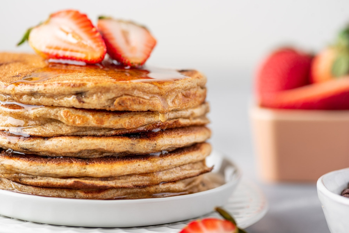 Greek Yogurt Pancakes with sliced strawberries on top served on the plate and dressed with sweet syrup
