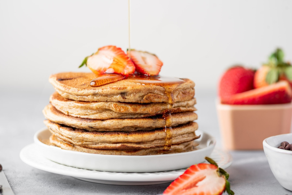Greek yogurt pancakes on top of each other served on the plate with sliced strawberry on top and dressed with syrup