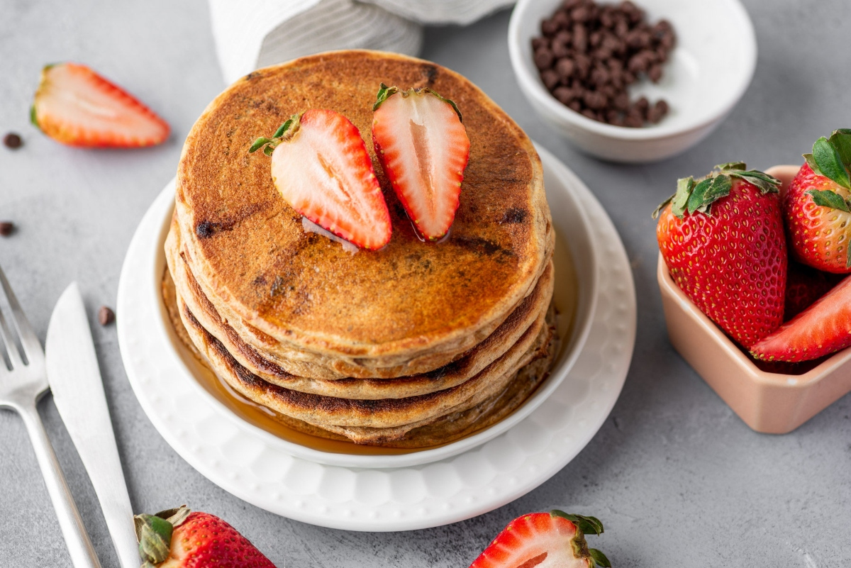 Greek yogurt pancakes pilled on top of each other on the plate with sliced strawberries on top and around the plate with bowl of chocolate nibs