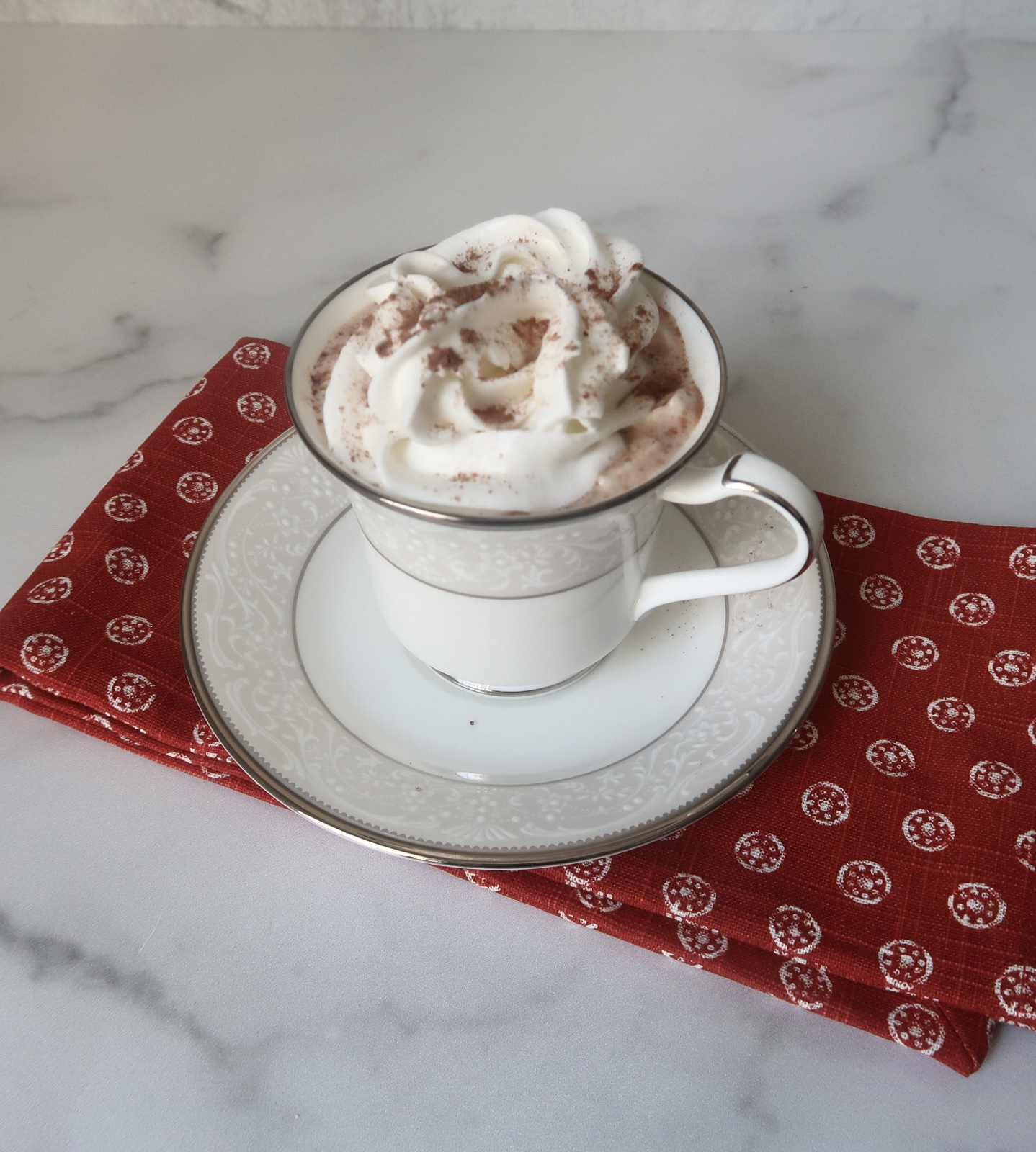 A white mug filled with low carb hot chocolate with whipped topping sits of a red towel on a marble countertop