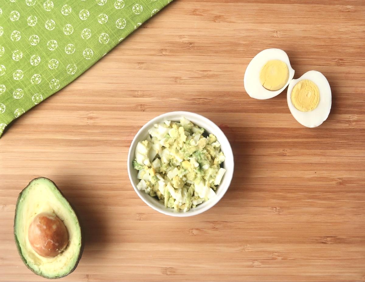 Avocado egg salad in white bowl next to sliced avocado and sliced hard boiled egg