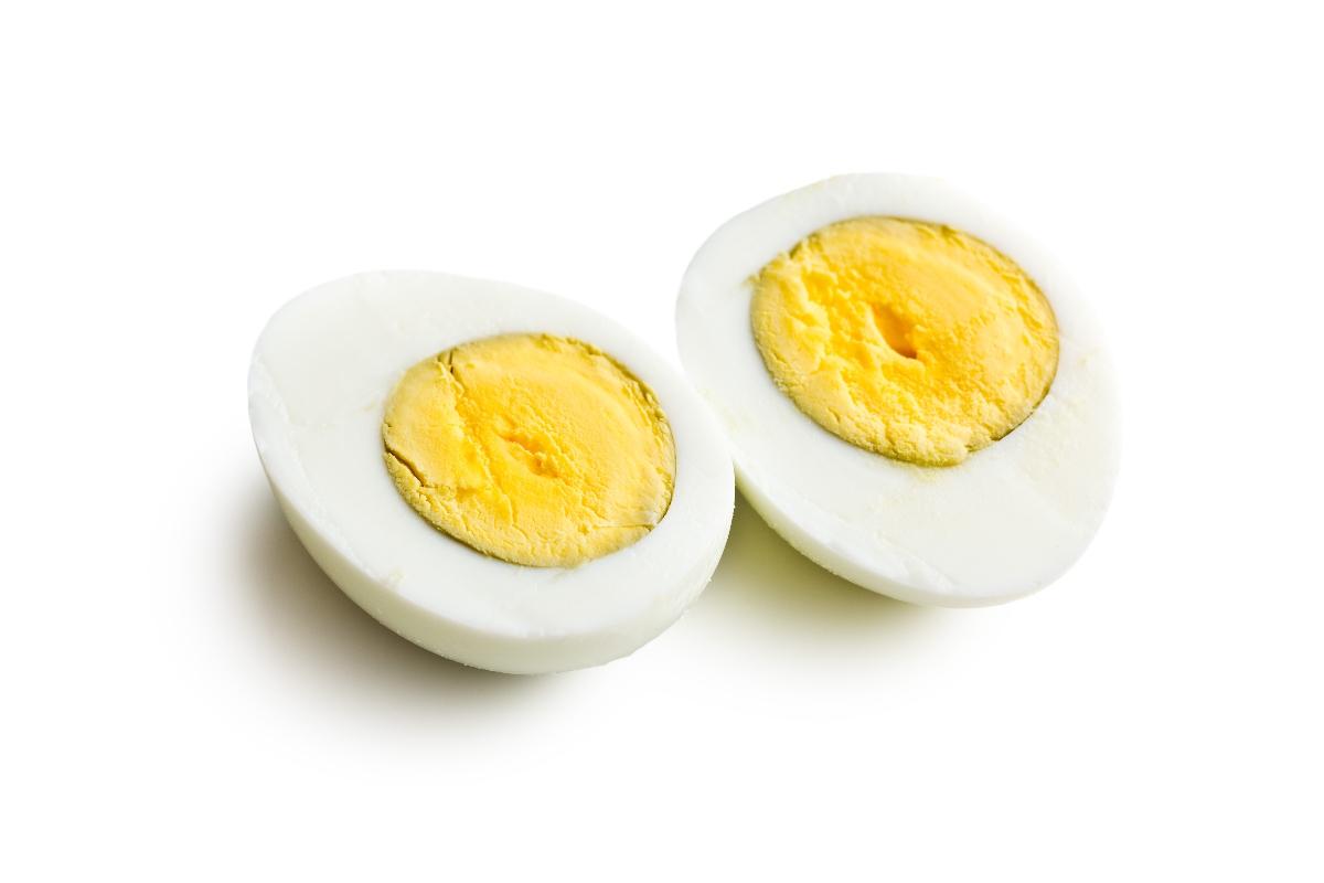 Hard boiled egg sliced vertically displaying yolk