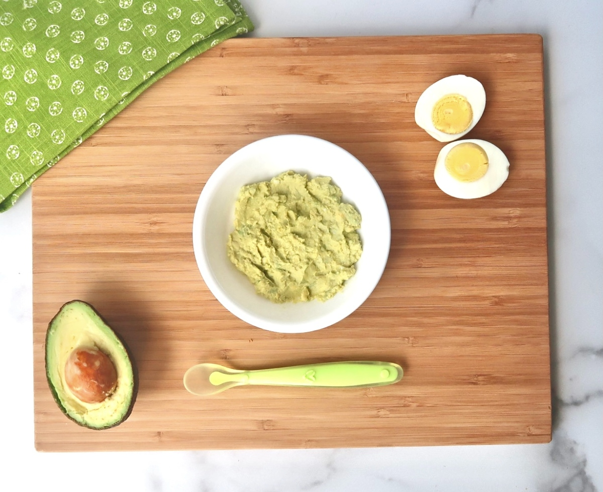 mashed avocado egg salad in white bowl with baby spoon, sliced avocado half, and sliced hard boiled egg