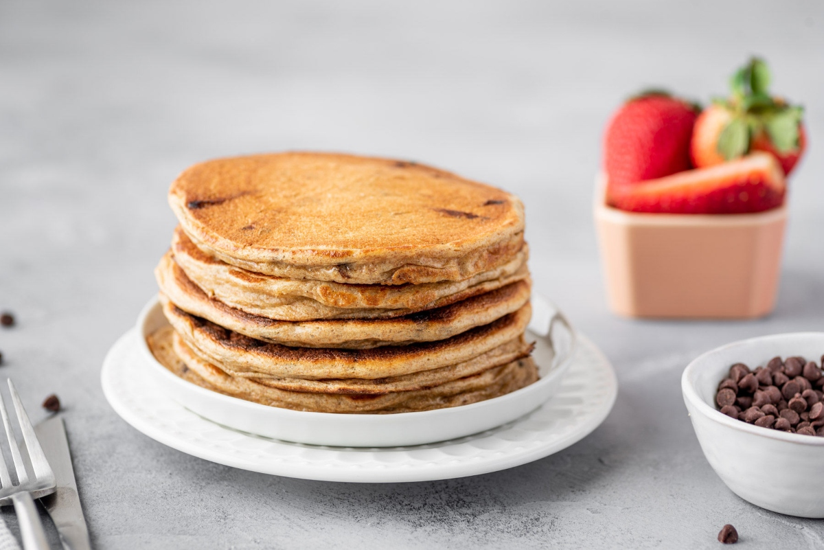 Greek yogurt pancakes pilled up together on a plate with bowl of strawberries in the background, served on the table