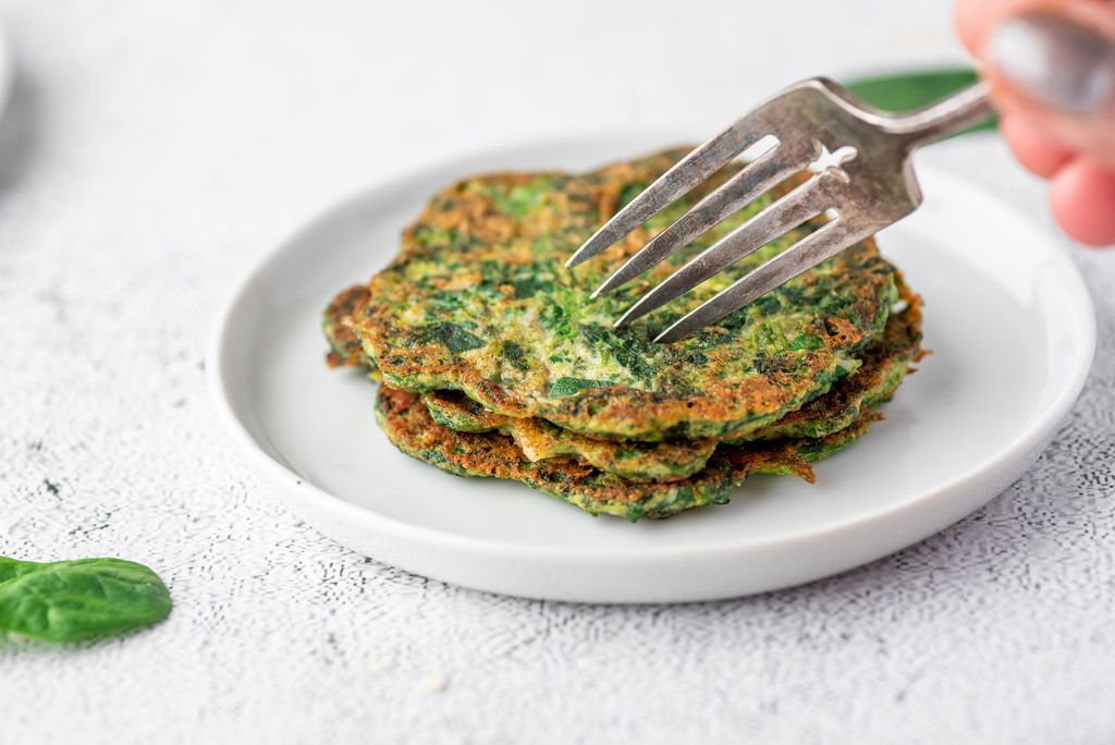 fork cutting into a stack of spinach pancakes on a white plate