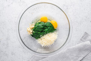 spinach eggs garlic and parmesan cheese in a glass bowl