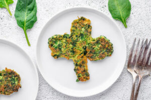 spinach pancake in the shape of a clover on a white plate with fork