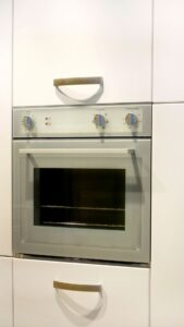 Oven build into white wood cabinet