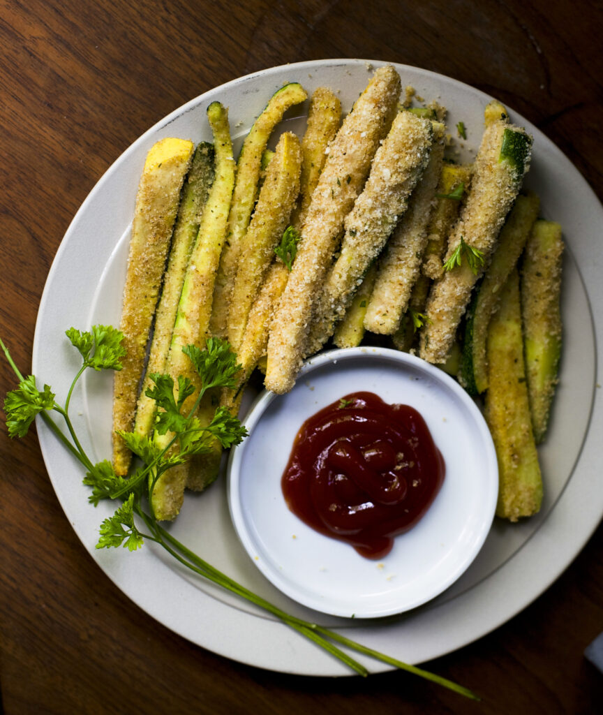 white plate of zucchini fries with a bowl of ketchup