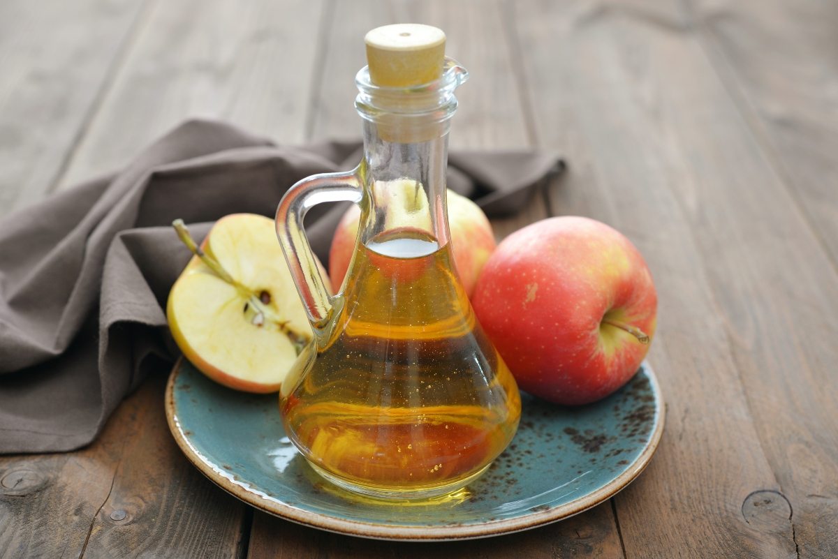 Apple cider vinegar in a bottle on the plate with chopped apples behind and a cloth napkin in the background