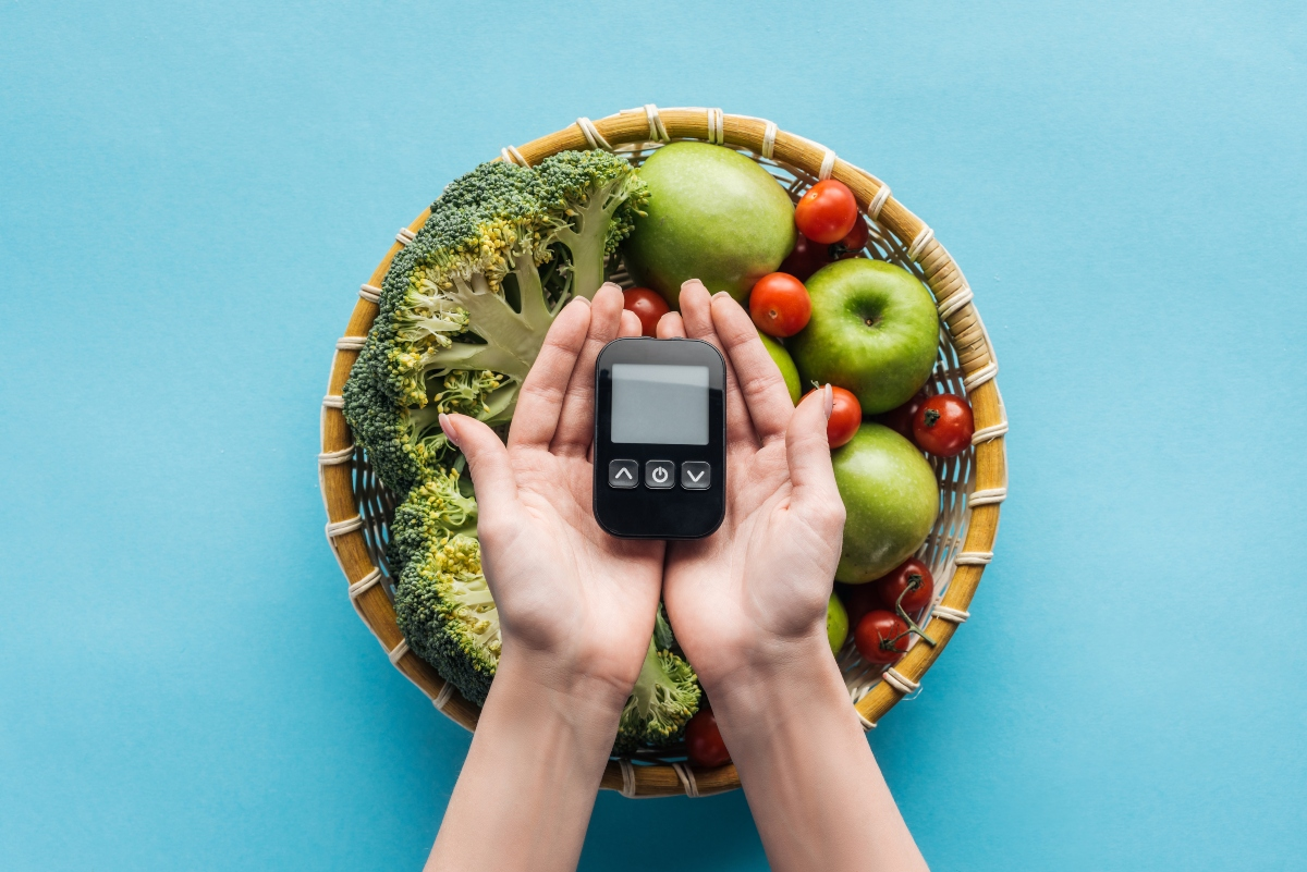 Hands holding blood sugar meter with bowl of vegies and fruits below the hands