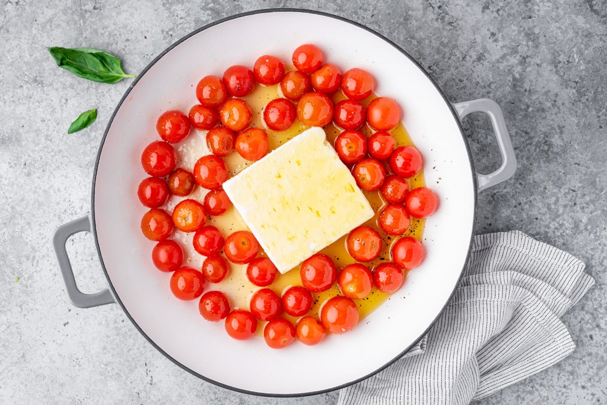 Cooking pot with cherry tomatoes, feta cheese and olive oil