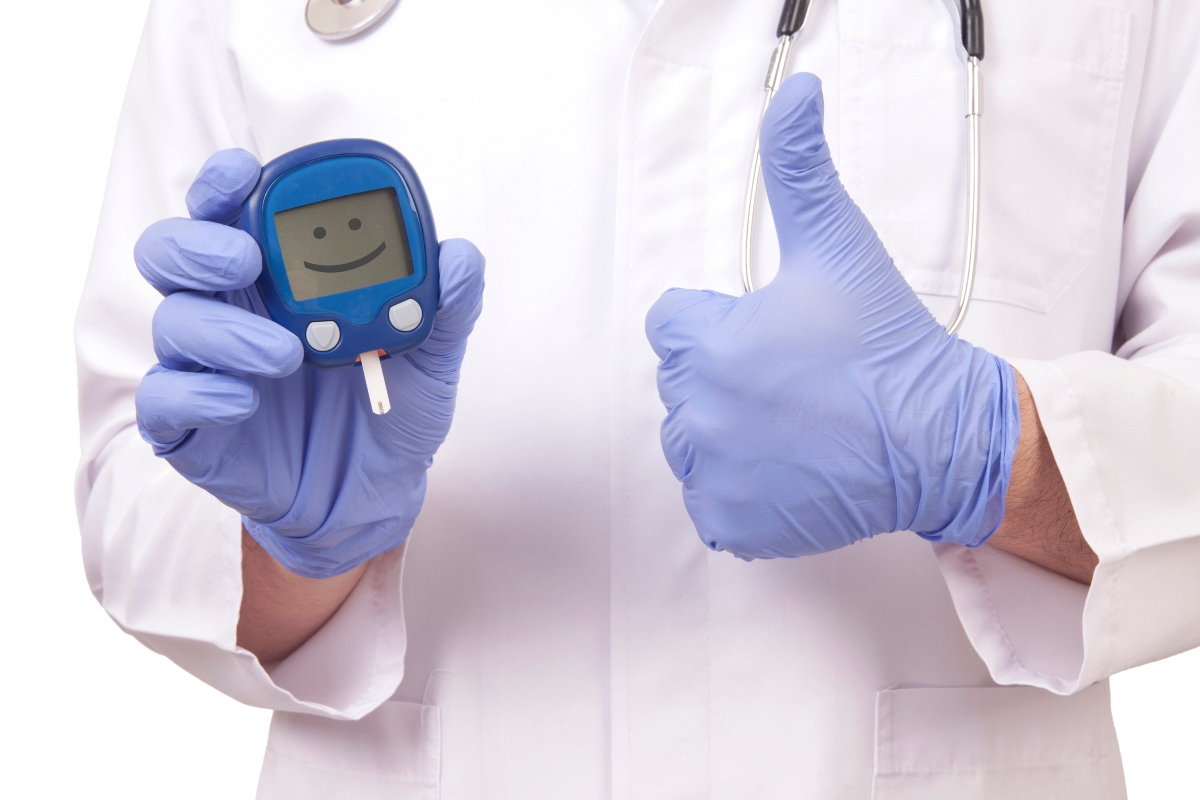 Doctors hand's holding blood sugar meter with a smiley on the screen and doctor giving thumb up