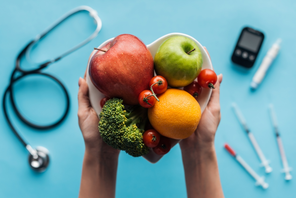Hand holding heart-shaped bowl of fruits and veggies with blood sugar meter, stethoscope and syringes