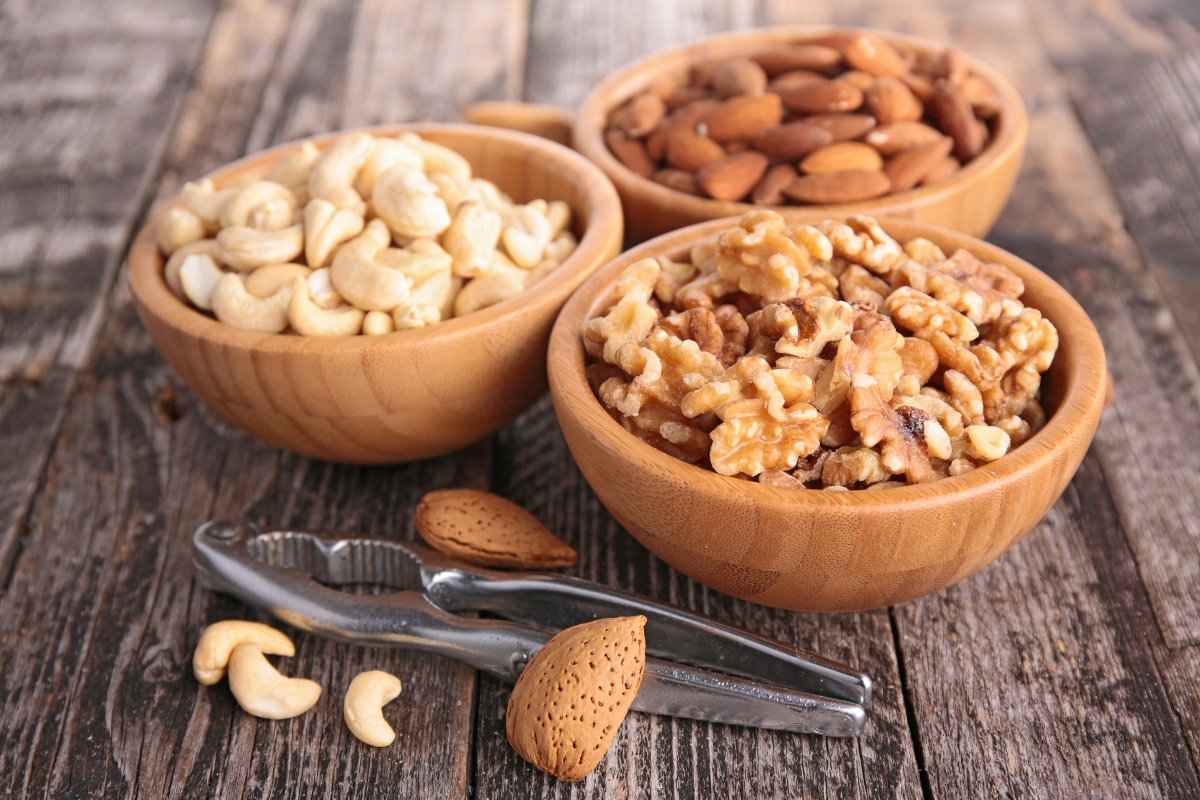 Walnuts, cashews and almonds in the bowls and a nutcracker in front of the bowls