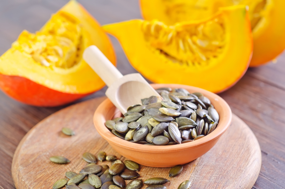 Pumpkin seeds in a bowl with a wooden spoon on cutting board with spread pumpkin seeds around a bowl, with chopped pumpkins in the background